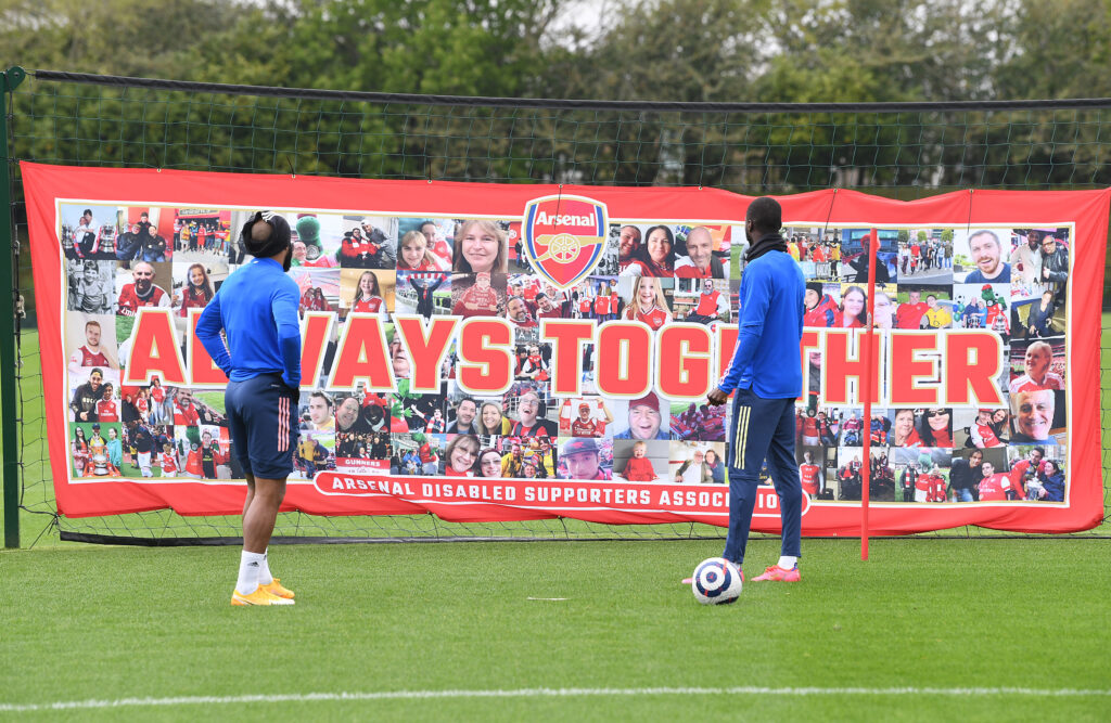 Pepe and Lacazette looking at the ADSA banner at the training ground.